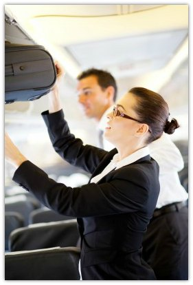 Flight attendant helping to store a carry on bag on a flight.